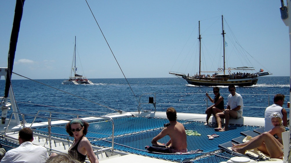 Show item 5 of 5. People lounging in the sun on a catamaran in Madeira Island