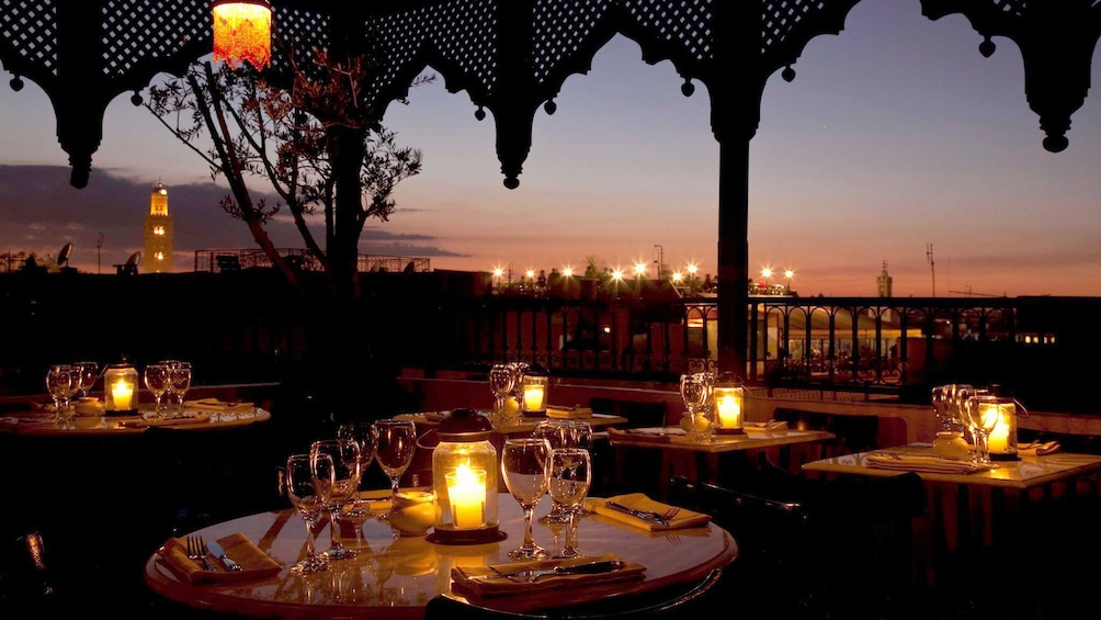 The outdoor seating area at Le Salama restaurant overlooking Jemaa el-Fnaa square at sunset