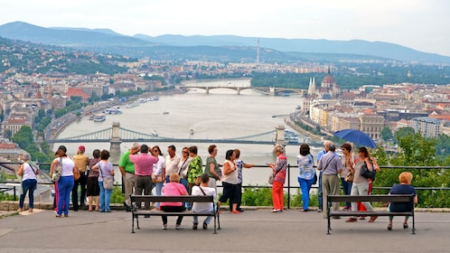 A group of people looking out at a river in budapest