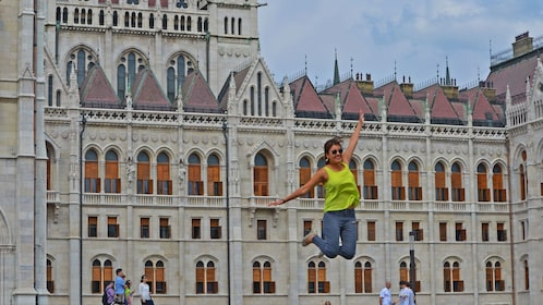 A woman jumping in front of a gothic style building in Budapest