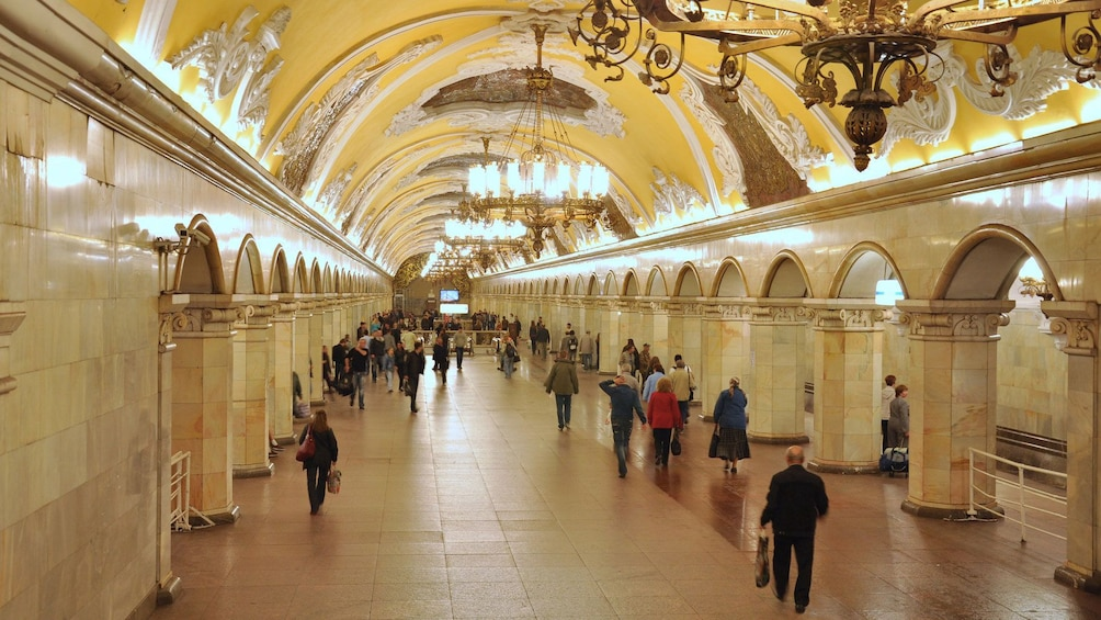 Show item 1 of 5. People surrounded by old world decorative motifs in a moscow metro station