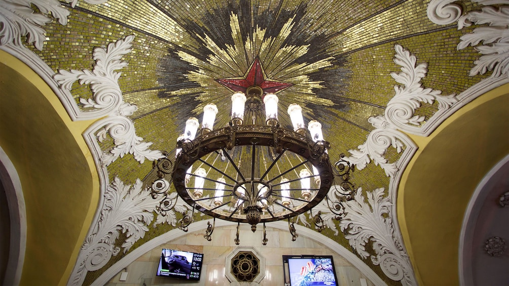 Show item 2 of 5. A chandelier illuminates the gilt mosaic ceiling of a moscow metro station