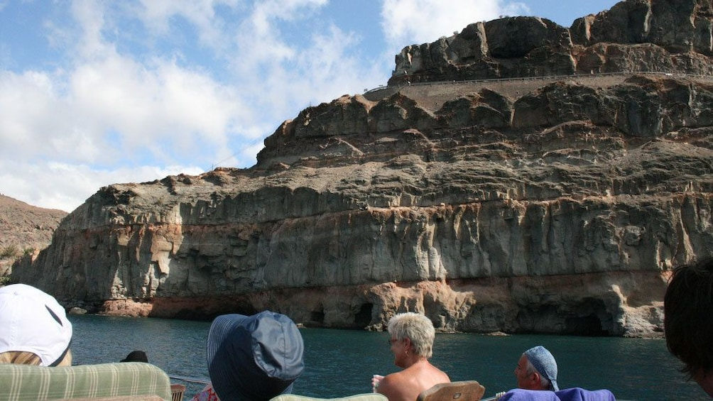 Show item 5 of 5. A Supercat Boat boat passing cliffs along the shore of Gran Canaria