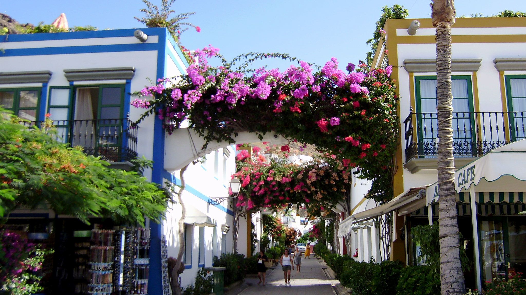 Flower-covered arches over a walkway between buildings in Gran Canaria