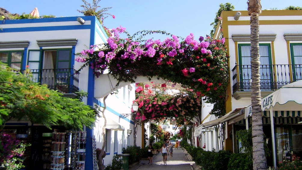 Åpne bilde 5 av 5. Flower-covered arches over a walkway between buildings in Gran Canaria