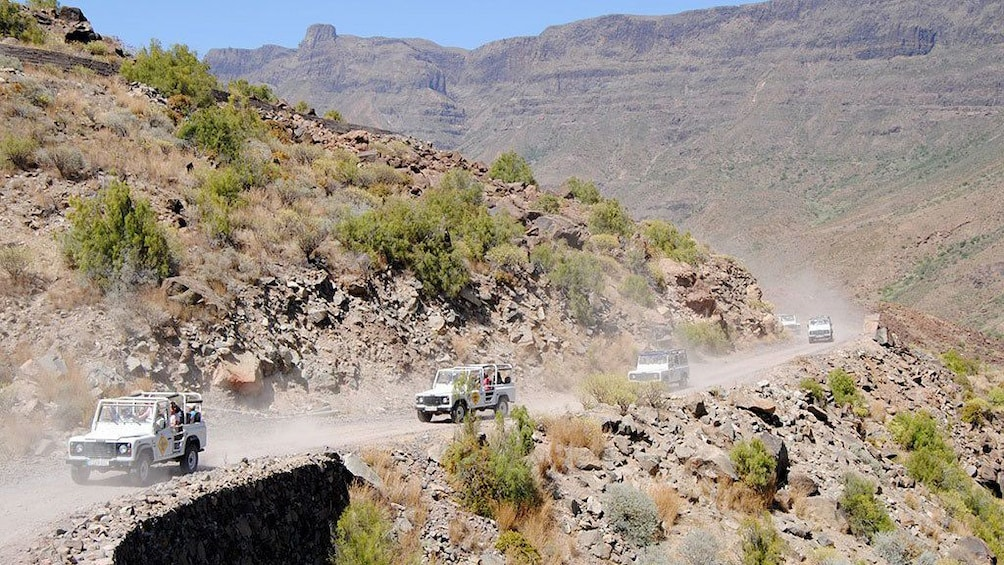 Show item 3 of 5. Jeeps on a winding hillside road in Gran Canaria