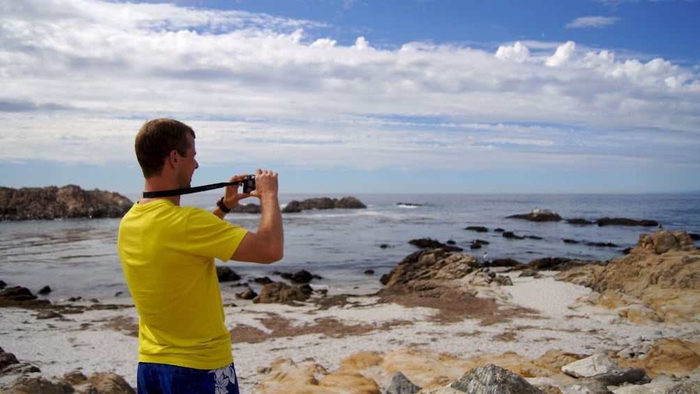 Show item 2 of 5. man taking pictures of the ocean from the beach in San Francisco
