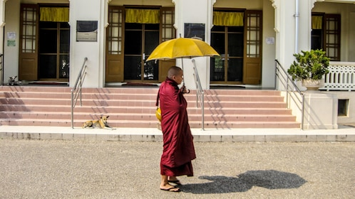 Mahasi Meditation Center monk in a red robe with an umbrella in Myanmar