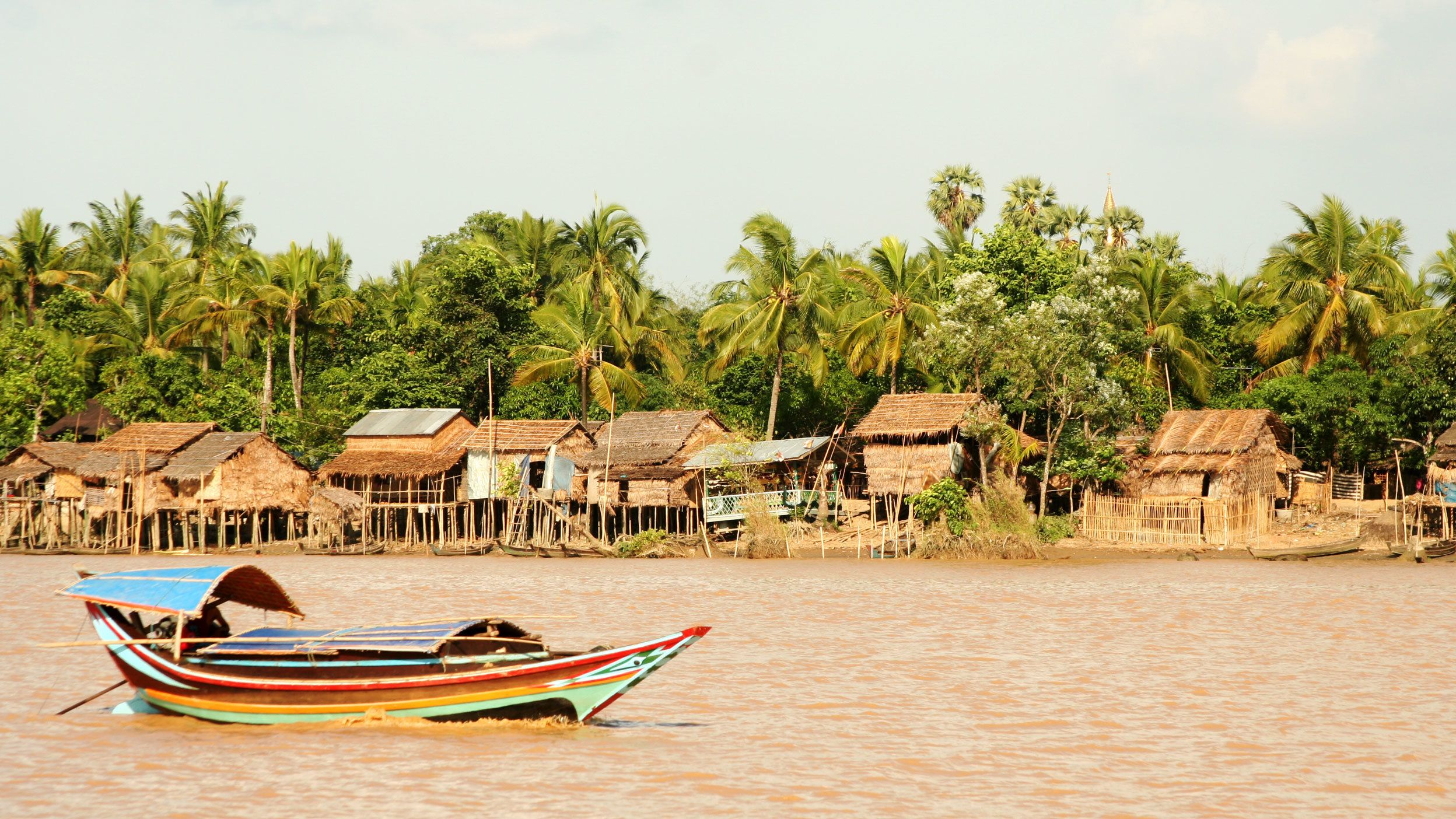Boat passing a village along the bank of the Yangon River in Myanmar