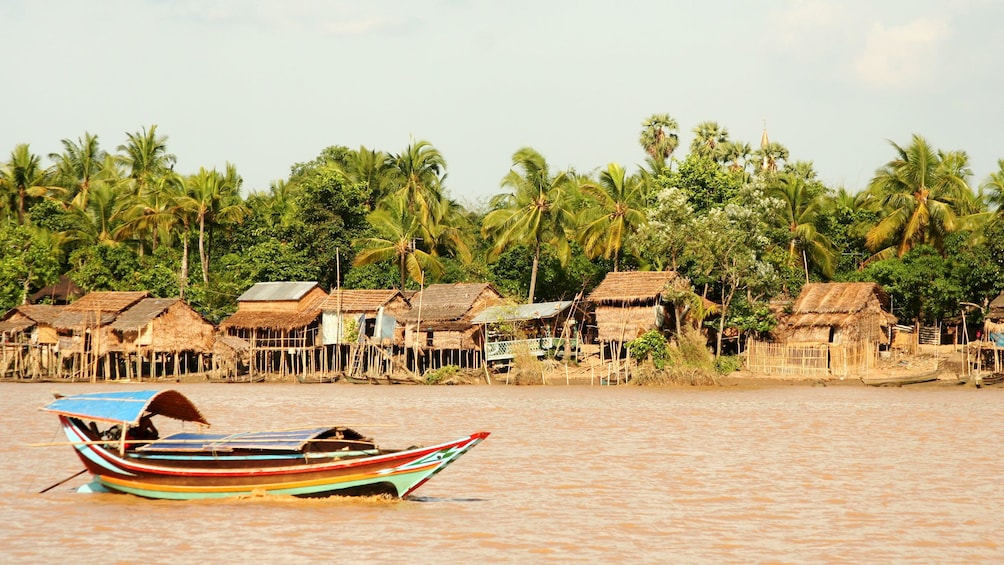 Show item 1 of 8. Boat passing a village along the bank of the Yangon River in Myanmar