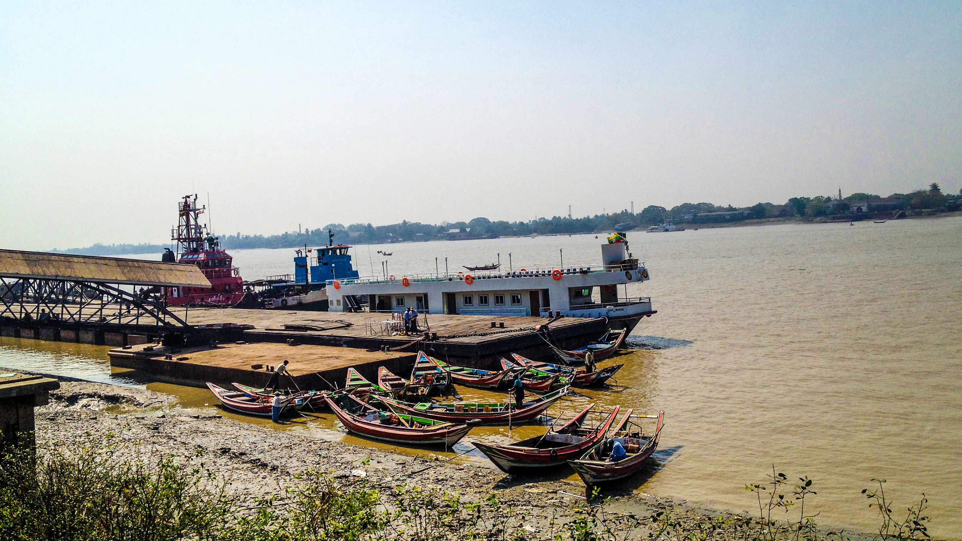 Boats docked on the bank of the Yangon River in Myanamar