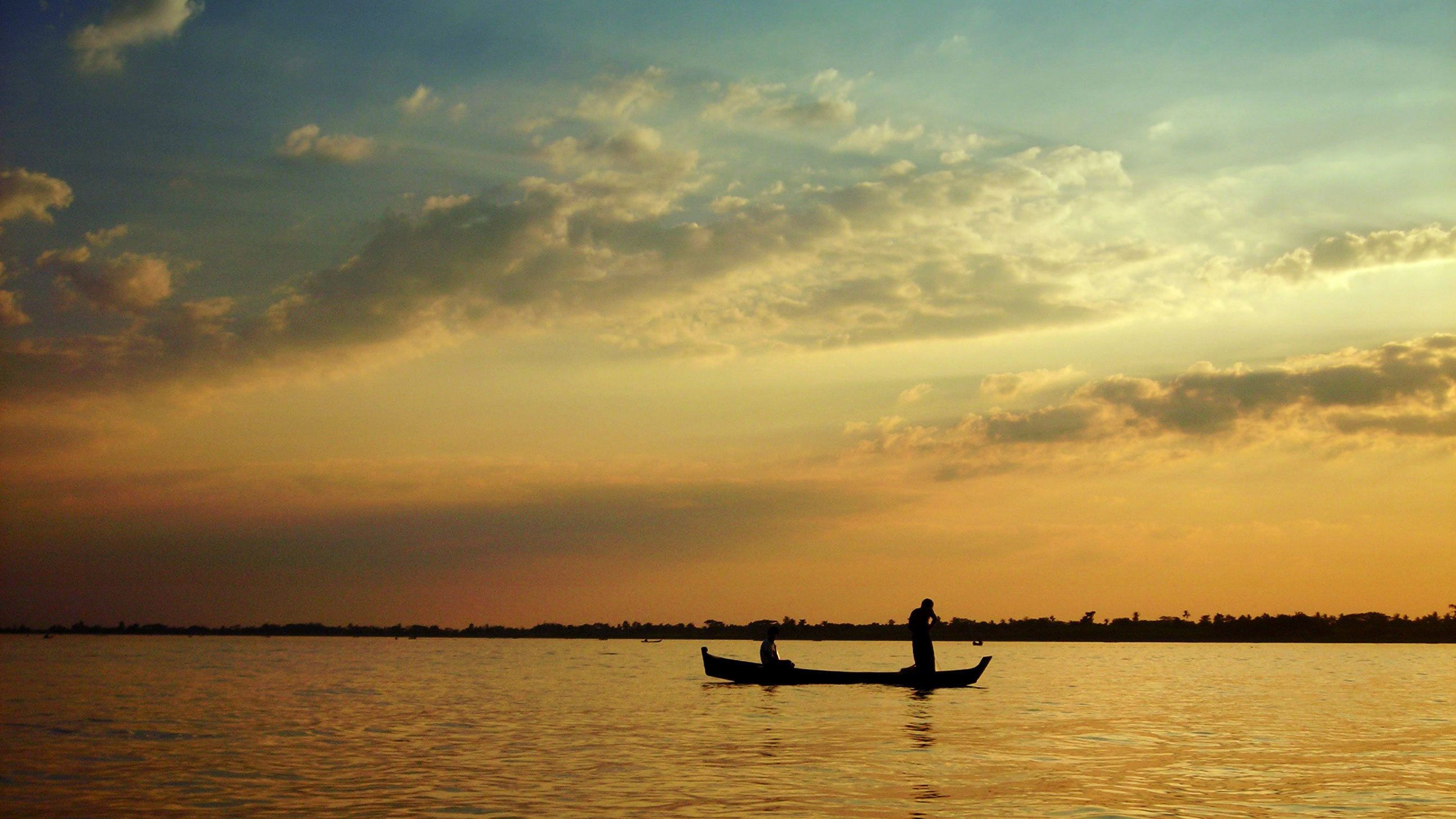 Silhouette of a boating couple on the Yangon River at sunset in Myanmar