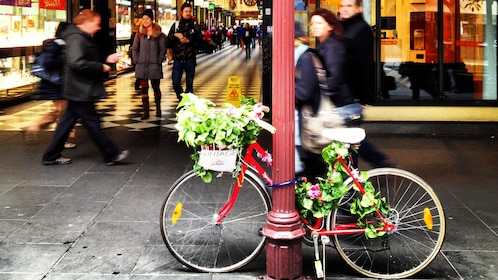 People pass by a bicycle chained to a light post in Melbourne