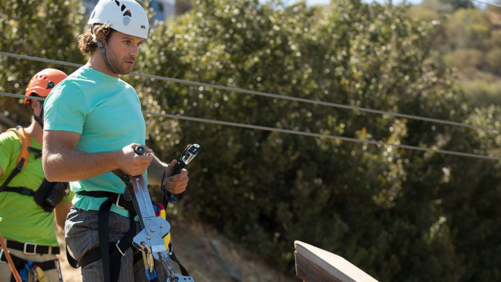 Ziplining man about to hook his harness to the cable on Catalina Island