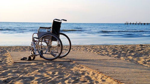 Wheelchair parked on a boarded path on the beach