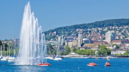 Tourists driving recreational boats on the water near the harbor in Zurich