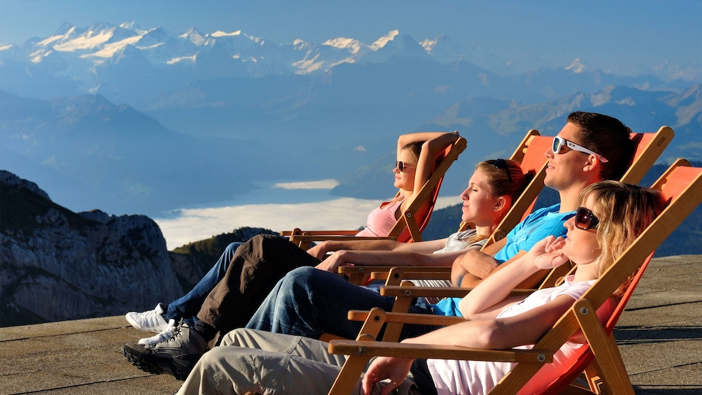 Show item 8 of 8. Group relaxing in lounge chairs in the sun on Mount Pilatus in Lucerne