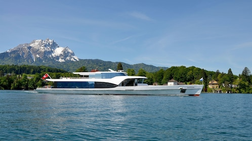 Tour boat on the water with mountain in the background in Lucerne