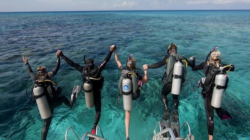 A group of scuba divers jumping from a boat in Antalya