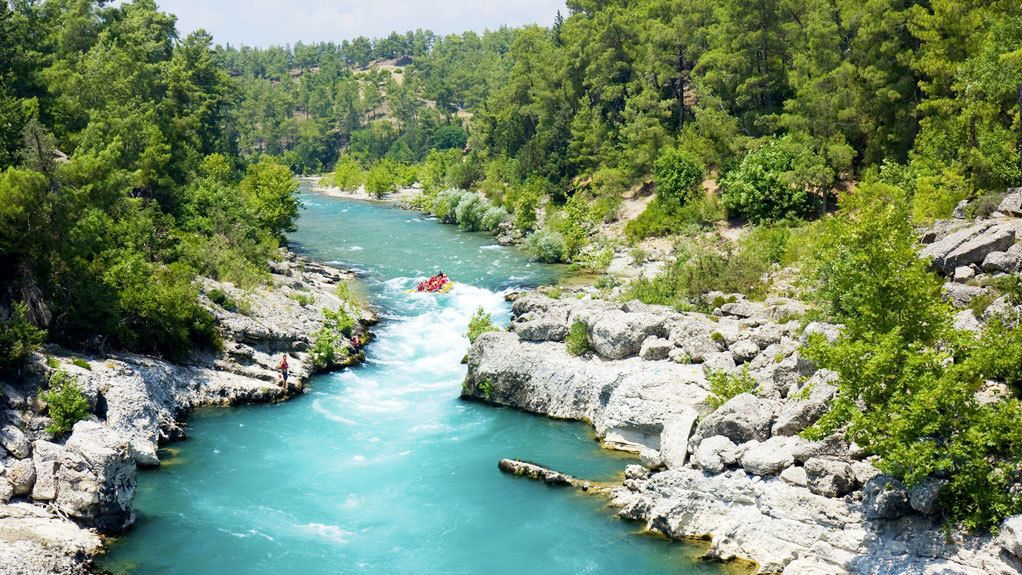 People in a raft making their way down a bright blue river in Antalya