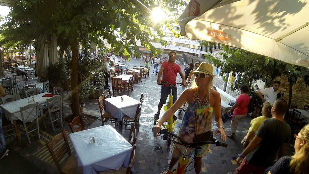 Show item 5 of 5. riding electric tri scooters through an outdoor dining area in Athens