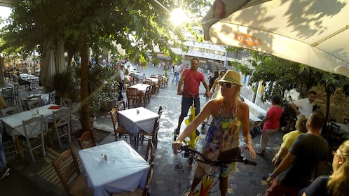 riding electric tri scooters through an outdoor dining area in Athens