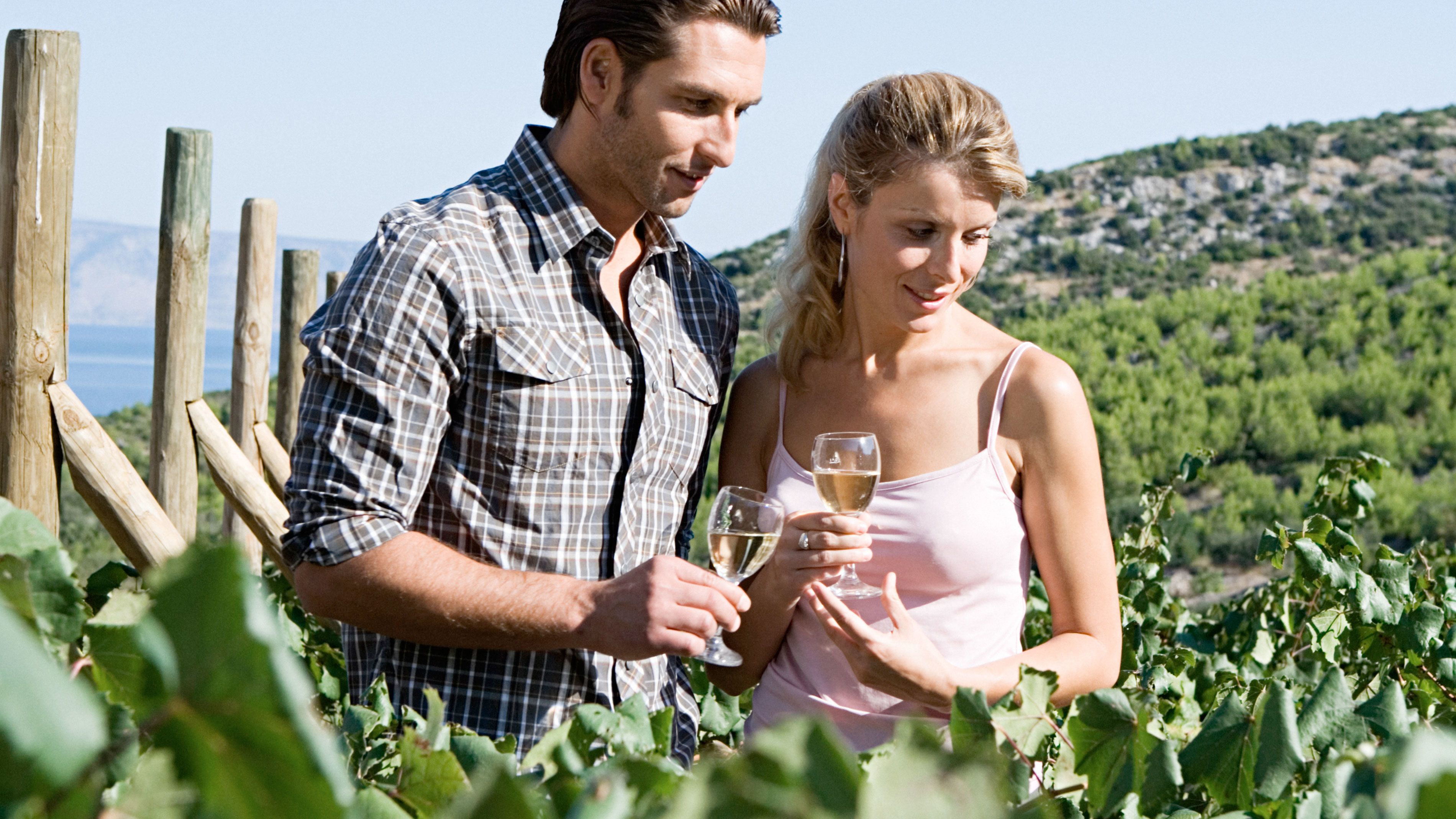 Couple holding wine glasses and standing in the vineyards in Sonoma