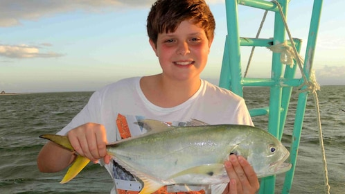 boy holding up a caught fish on the boat in Mexico