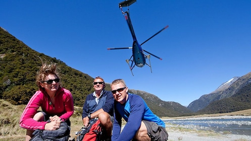group squatting beneath a hovering helicopter in New Zealand