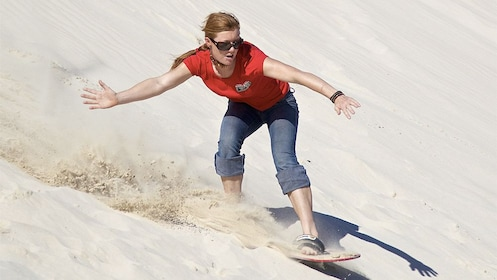 woman sand boarding down a sand dune in Australia