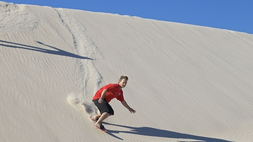 man sand boarding down a steep sand dune in Australia