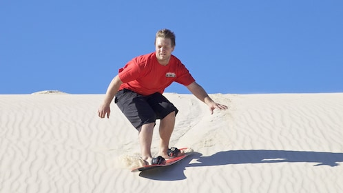 man sand boarding from the top of a sand dune in Australia