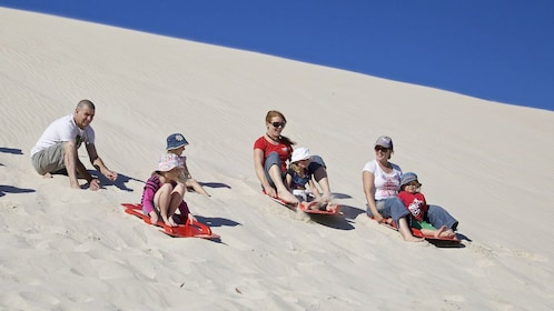 group sledding down the sand dunes with children in Australia