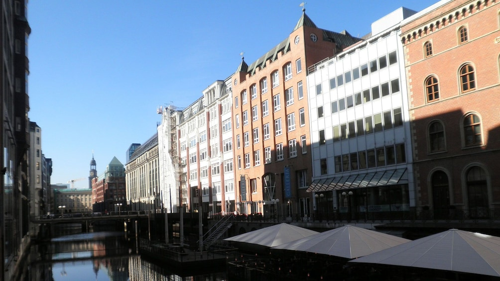 Show item 3 of 5. buildings casting long shadows along the water channel in Hamburg