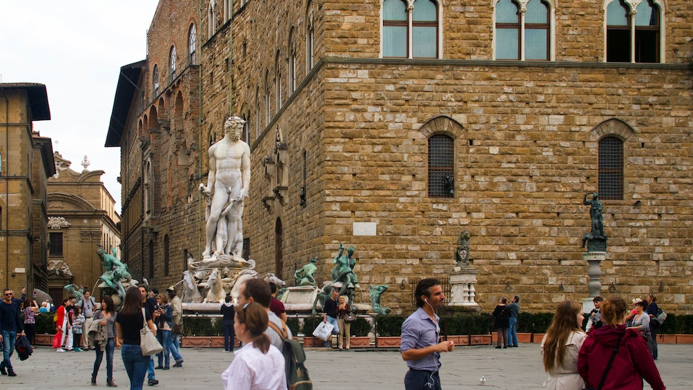 crowds walking by a marble statue in Florence