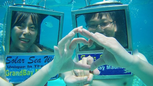 couple holding hands under water