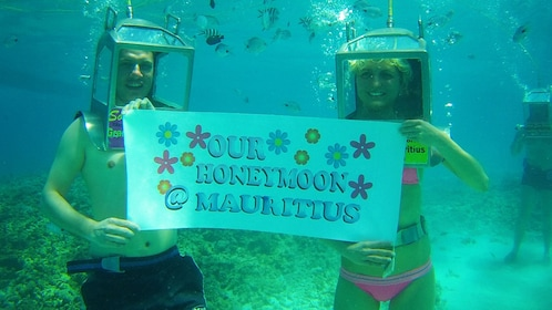 couple holding sign underwater