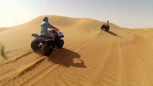 Tourists riding along the sand dunes in ATVs