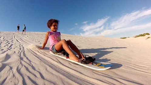 Child sledding down a sand dune near Cape Town