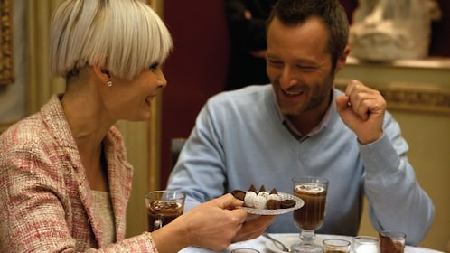 Couple enjoying hot chocolate and a small plate of candies in Turin