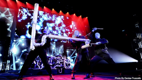 Three energetic characters of the Blue Man Group performing at a show in Las Vegas