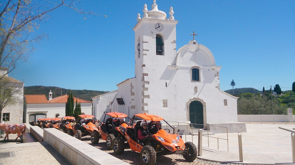 Charger l'élément 1 sur 5. Line of dune buggies near a cathedral in Algarve