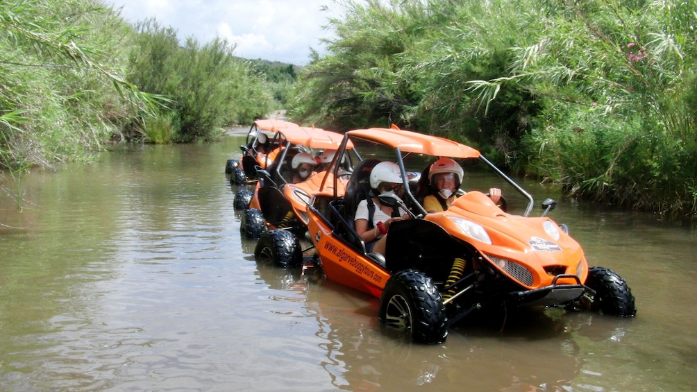 Show item 3 of 5. Row of dune buggies driving through a shallow river in Algarve