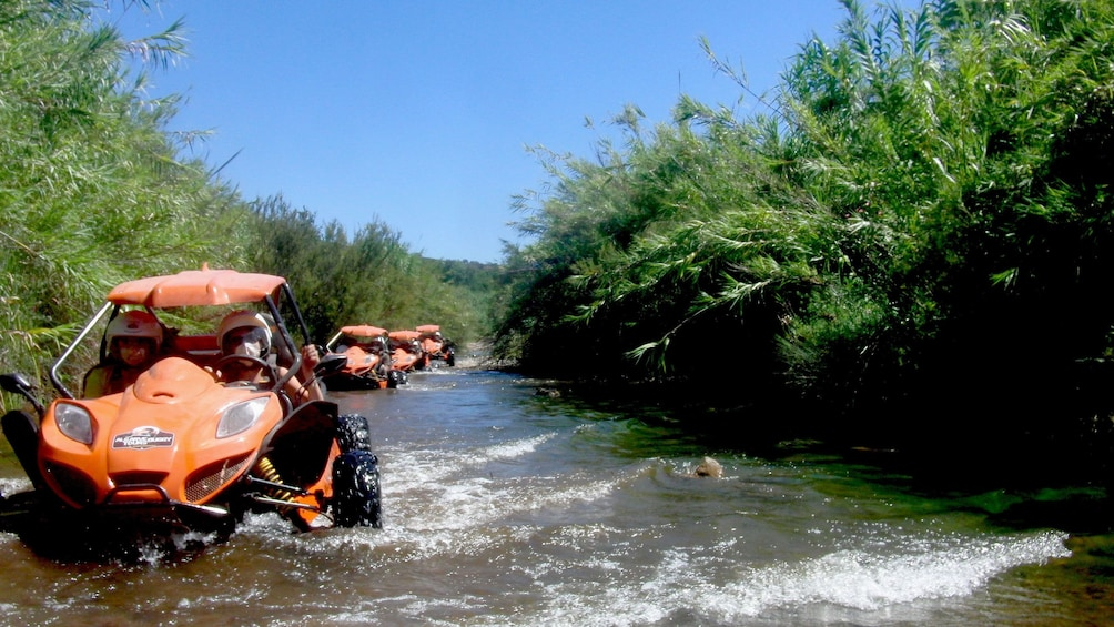 Charger l'élément 1 sur 5. Line of dune buggies driving in the water of a shallow river in Algarve
