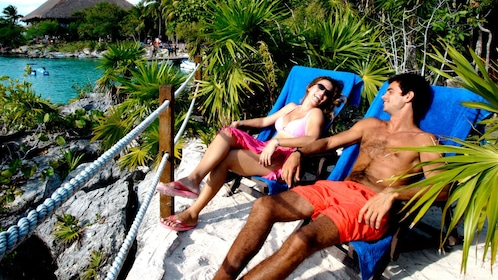 Couple lounging in beach chairs at Xel Ha Park in Riviera Maya
