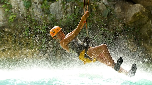 Helmeted woman in a harness splashing down onto the water at Xplor Park in Riviera Maya