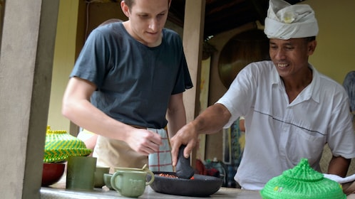 Chef teaching a man to cook Balinese food in Bali