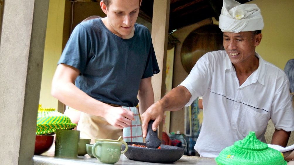 Show item 1 of 5. Chef teaching a man to cook Balinese food in Bali