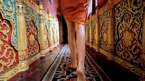 Woman walking down ornately decorated hallway at a spa in Bali