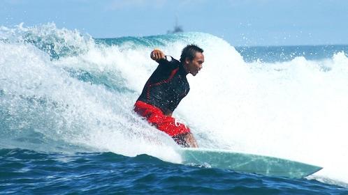 Surfing man in the water in Kuta
